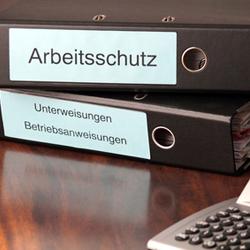 Arbeitsschutzordner mit Taschenrechner auf Chef Schreibtisch